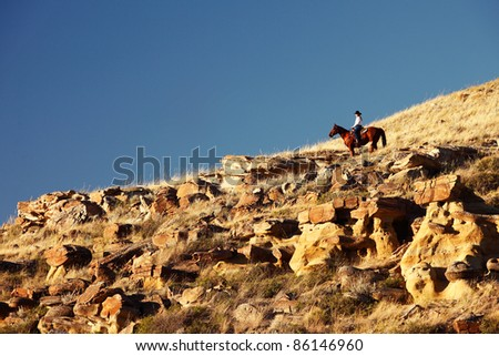A person in the distance riding a quarter horse on top of a rocky, western hilltop against a clear, blue sky. - stock photo