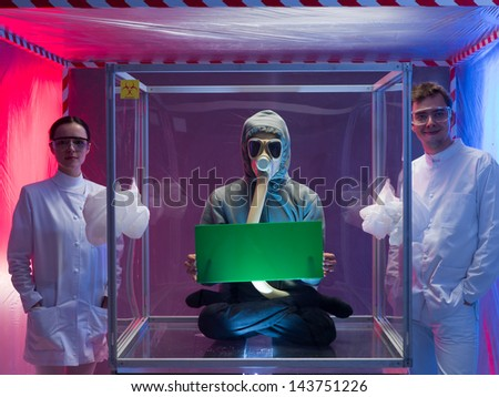 a person inside a protective enclosure, wearing a gas mask, holding a green board with both hands, with two scientists, a man and a woman outside the box, all inside a containment tent