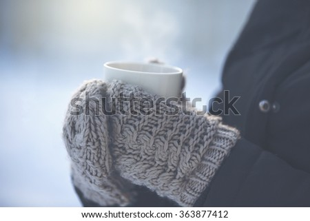 A person is holding a cup of hot drink outdoor. The weather is very cold and the mug is smoking. The person has a jacket and wool mittens in her hands. Image has vintage effect applied. - stock photo