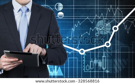 A person is looking for some data using the electronic device. Financial charts are drawn on the background - stock photo