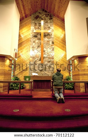 A person is praying alone in a quiet church. - stock photo