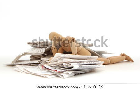 A person lies in despair in a pile of receipts - stock photo