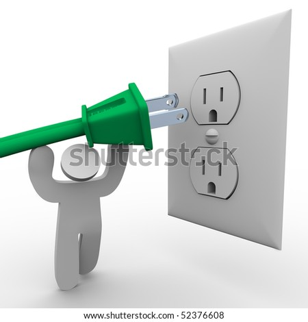 A person lifts a green electrical plug up to the power outlet - stock photo