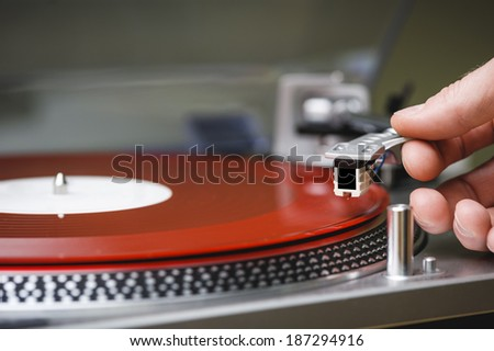a person placing the needle on a record. - stock photo