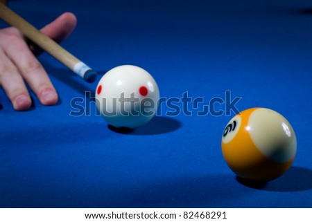 A person playing billiard is about to hit the white ball - stock photo