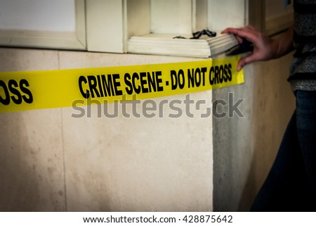 "A person posting a ""CRIME SCENE DO NOT PASS"" sign and sticking it to a well."