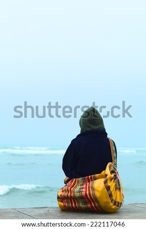 A person sitting on the coast and watching the sea on the shore of  Lima, Peru in winter - stock photo