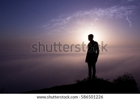 A person standing in golden light during sunrise time on hill. Silhouette of a person in nature with foggy morning.