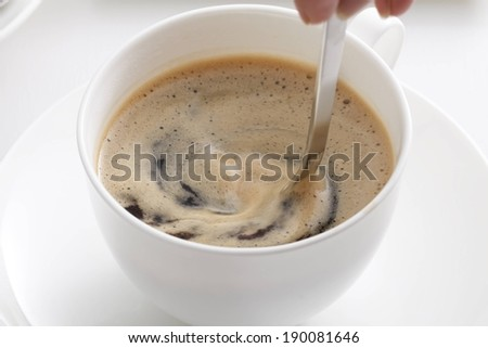 A person using a spoon to stir a coffee drink. - stock photo