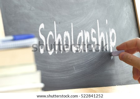A person writing the word Scholarship on a blackboard. Some school materials and copy space.