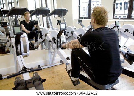 A personal trainer / fitness instructor working out on a rowing machine in a modern gym - stock photo