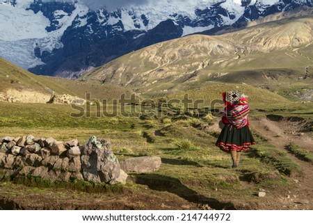 A Peruvian woman walking with a child on her back in South American Andes - stock photo
