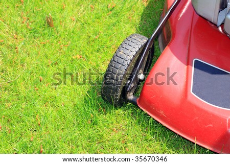 A petrol driven lawn mower with rubber tyres ready to cut a green lawn. - stock photo