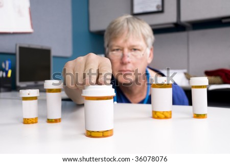 A pharmacist selects the right medication for his patient.  Labels are blank to allow for copy to be placed on the pill bottles.