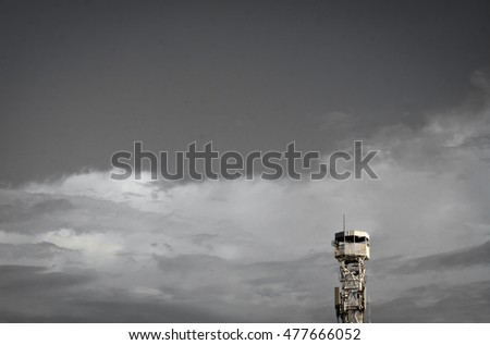 A phone reception tower. telecoms transmitter on sky and clouds. Telecommunications tower, painted white and red in a day of clear sky.