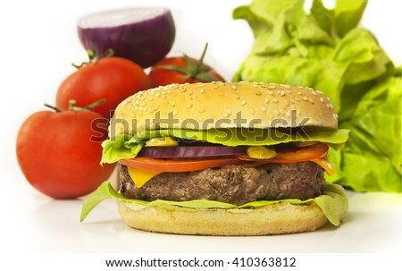 A photo of a burger with leaves of green lettuce, slices of Cheddar cheese, gherkins, red onions, tomatoes, and a thick meat patty, with blurred vegetables in the background - stock photo