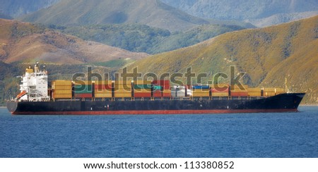 A photo of a cargo ship sailing in still water - stock photo