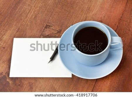 A photo of a cup of coffee with a black ink pen and a blank white post card with copyspace, on a dark wooden texture, with a place for text