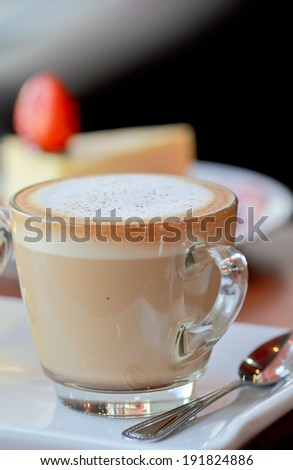a photo of a cup of coffee with strawberry cheese cake background