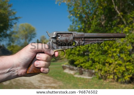A photo of a hand holding an antique handgun in a shooting position. It is an outdoor photo on a sunny day with a blue sky and green foliage background - stock photo