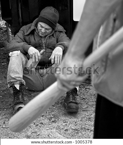 A photo of a homeless man sitting against a dumpster, with a teen holding a bat approaching.  Black & white and film grain effects added for drama. - stock photo