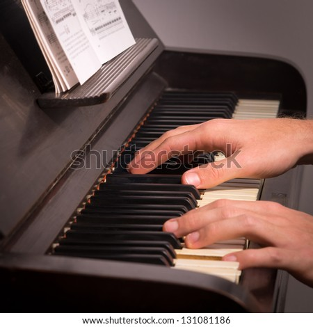 a photo of a man playing on a piano - stock photo