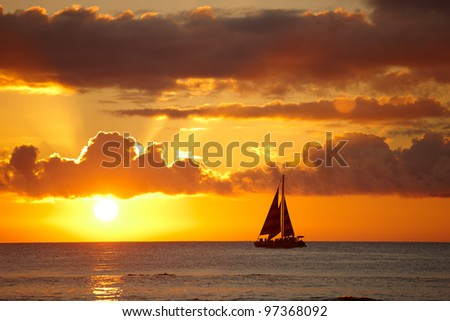 A photo of a sail boat in sunset