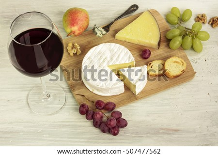 A photo of a tasting with a glass of red wine, different types of cheese, bread, nuts, pear, grapes, on a wooden board with copyspace