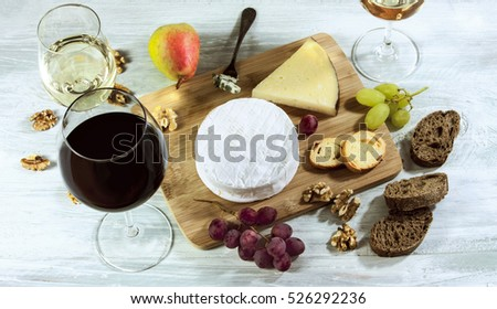 A photo of a tasting with glasses of wine, red and white, different types of cheese, bread, nuts, pear, grapes, on a wooden board