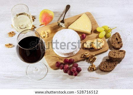 A photo of a tasting with glasses of wine, red and white, different types of cheese, bread, nuts, pear, grapes, on a wooden board with copyspace