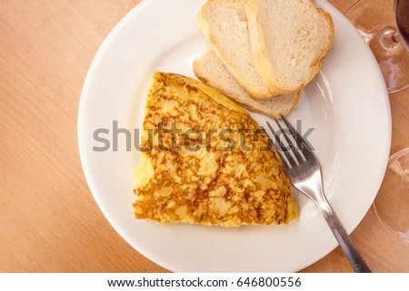 A photo of a tortilla, traditional Spanish potato omelette, with a fork, white bread, glasses of red wine. Typical tapas, slightly toned image