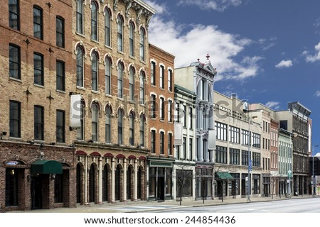 A photo of a typical small town main street in the United States of America. Features old brick buildings with specialty shops and restaurants.  - stock photo