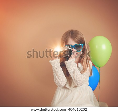A photo of a vintage child taking a picture with an old camera against a blank wall with balloons for a creativity or vision concept. - stock photo
