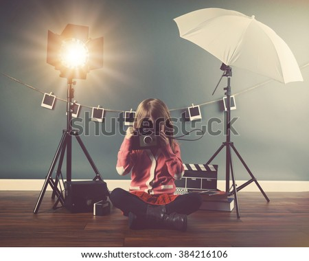 A photo of a vintage child taking a picture with an old camera in a studio with lights and film for a creativity or vision concept. - stock photo