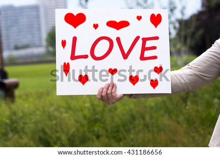 a photo of a woman with a piece of card -  I love you - stock photo