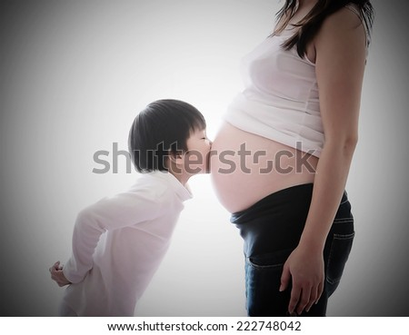 a photo of asian boy kiss belly pregnant asian woman ,vintage style - stock photo