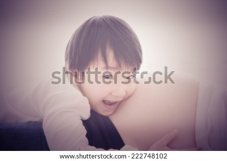 a photo of asian boy listening belly pregnant ,vintage style - stock photo