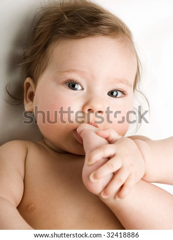 A photo of baby taking his feet in his mouth - stock photo