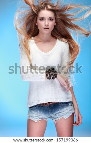 A photo of beautiful girl is in fashion style ,on a blue background,
