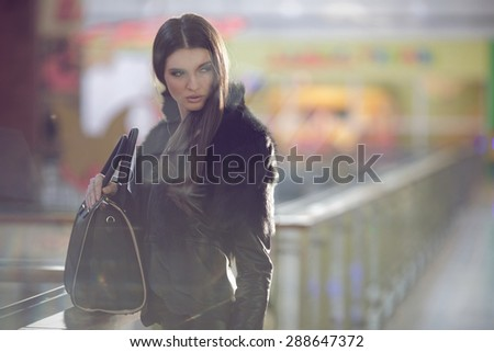 A photo of beautiful girl with a bag is in fashion style, glamour. Fashion photo of young magnificent woman.Fine art. Natural light. - stock photo