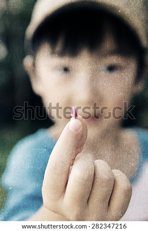 a photo of boy holding little flower bud,with fabric texture - stock photo
