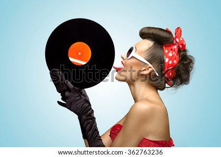 A photo of glamorous pin-up girl touching vinyl LP with tongue. - stock photo
