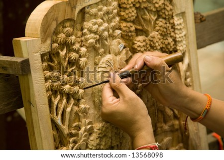 A photo of hands with tool, engraving wood - stock photo