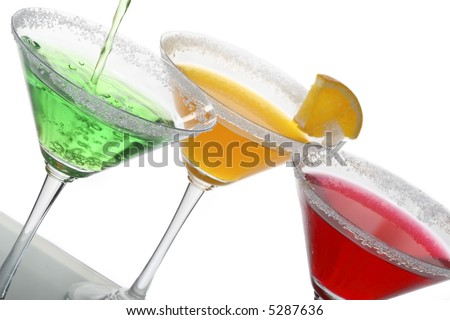 a photo of martini glass with green, orange cocktail and a piece of citrus