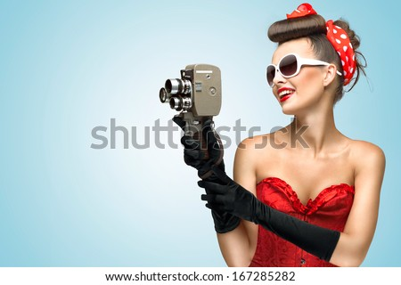 A photo of the pin-up girl in corset and gloves holding vintage 8mm camera. - stock photo