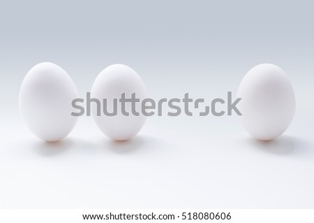 A photo of three white eggs on the grey background.