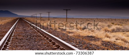 A photograph of a railroad.  The sharp metal rails are pulling your eye through the photograph. - stock photo