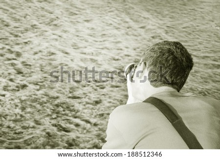 a photographer photographing the ocean black and white tones - stock photo