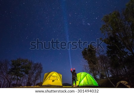 a photographer point a flashlight in to the sky between camp in forest at night with star - stock photo