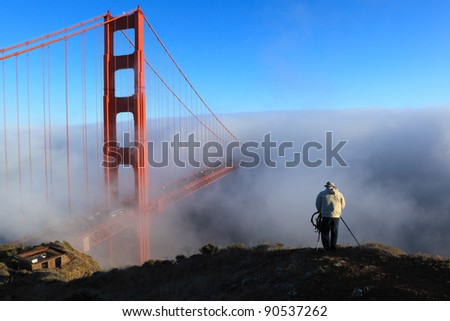 A photographer takes pictures  Golden Gate Bridge in a fog. San Francisco, California